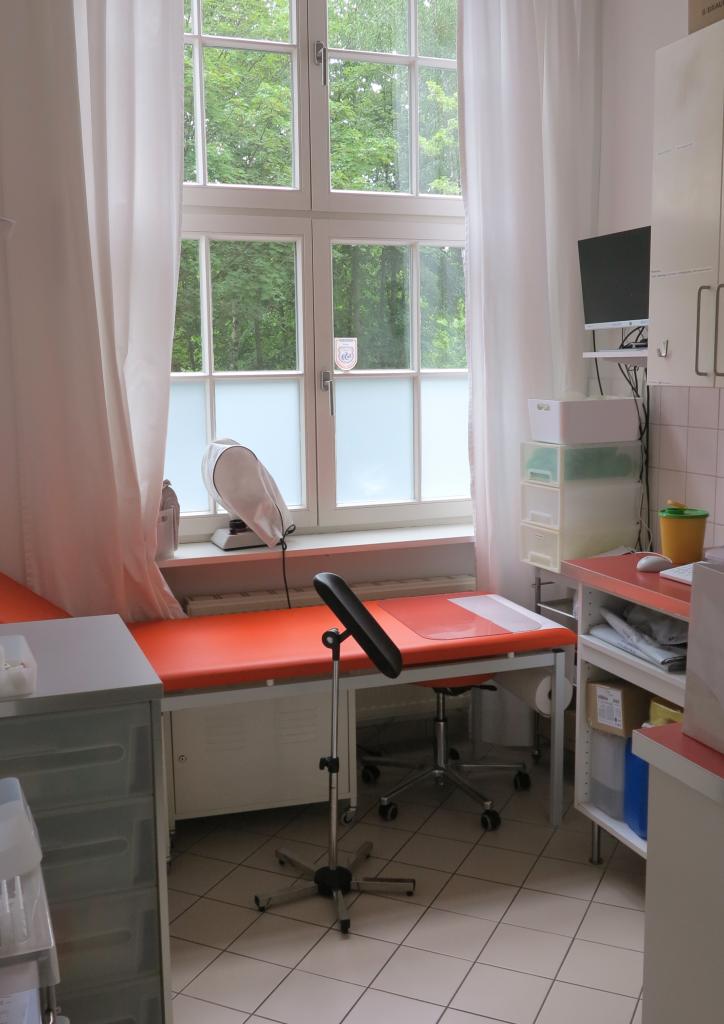 In einem engen aber lichtdurchfluteten Behandlungszimmer einer allgemeinmedizinischen Praxis steht eine nicht höhenverstellbare Untersuchungsliege.