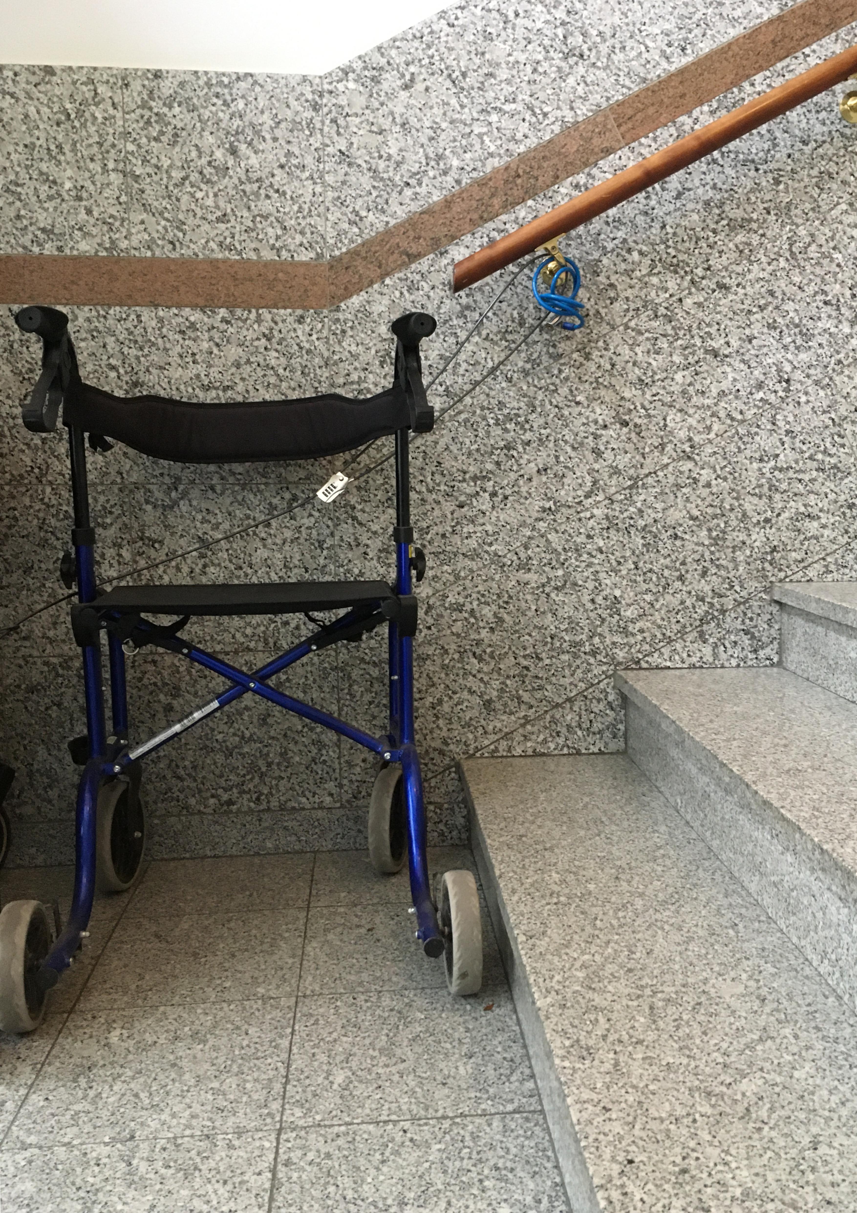 In dem Treppenhaus einer orthopädischen Praxis steht am Fußende einer Treppe ein Rollator.
